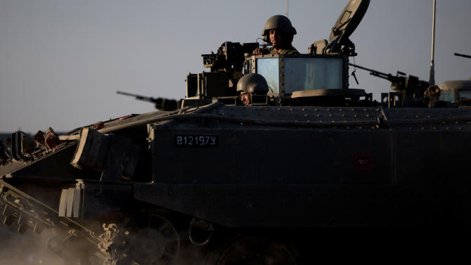 """Israeli soldiers ride on top of an armored personal carrier close to the Israel Gaza Border, southern Israel, Thursday, Nov. 15, 2012. Israel's prime minister says the army is prepared for a """"significant widening"""" of its operation in the Gaza Strip. Benjamin Netanyahu told reporters on Thursday that Israel has """"made it clear"""" it won't tolerate continued rocket fire on its civilians. (AP Photo/Ariel Schalit)"""