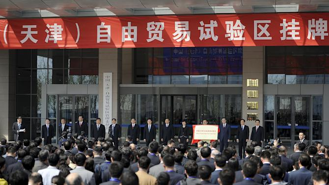 """People look on as Tianjin municipal officials stand behind a sign reading """"China (Tianjin) Pilot Free Trade Zone"""", at an unveiling ceremony in Tianjin municipality"""