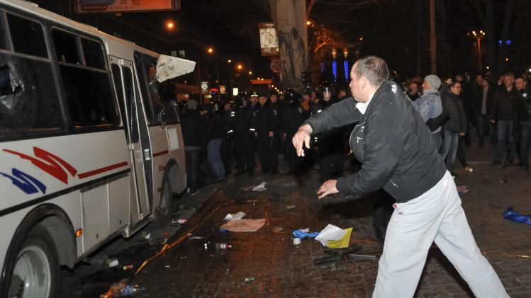 A pro-Russia protestor throws a stone at a police bus in which pro-Ukraine and anti-war demonstrators were held after clashes during their rallies in Donetsk