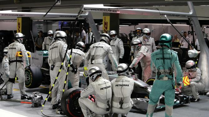 Mercedes Formula One crew surround the car of driver Nico Rosberg of Germany after it came into the pitlane during the Singapore F1 Grand Prix in Singapore