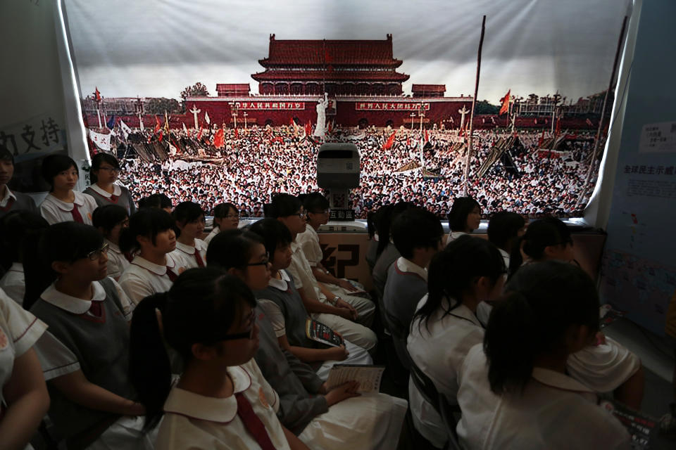 Students watch video footage of the crackdown of the June 4, 1989 pro-democracy movement in Beijing's Tiananmen Square at the June 4 Memorial Museum run by pro-democracy activists in Hong Kong Monday, June 4, 2012 to commemorate the 23rd anniversary of the bloodshed. (AP Photo/Vincent Yu)