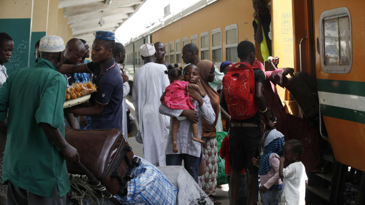 In this Photo taken, Friday, March . 8, 2013, Passengers board an Ooni of Ife train to Kano, in Lagos, Nigeria.  Nigeria reopened its train line to the north Dec. 21, marking the end of a $166 million project to rebuild portions of the abandoned line washed out years earlier. The state-owned China Civil Engineering Construction Corp. rebuilt the southern portion of the line, while a Nigerian company handled the rest. (AP Photo/Sunday Alamba)
