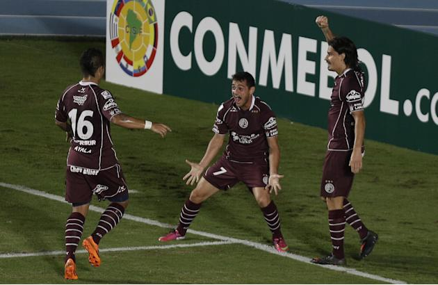 Lautaro Acosta of Argentina's Lanus, center, celebrates with teammates after scoring a goal against Colombia's Deportivo Cali during a Copa Libertadores soccer match in Cali, Colombia, Thursda
