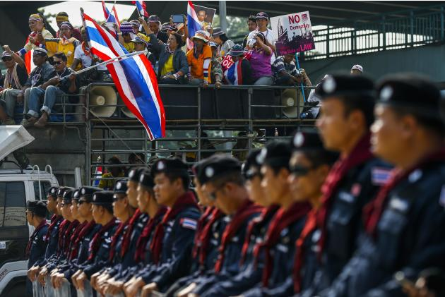 Anti-government protesters gather on a truck as riot policemen stand guard in Bangkok