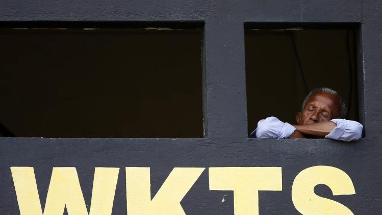 An official sleeps at a score board during the second day of the second test cricket match between South Africa and Sri Lanka in Colombo