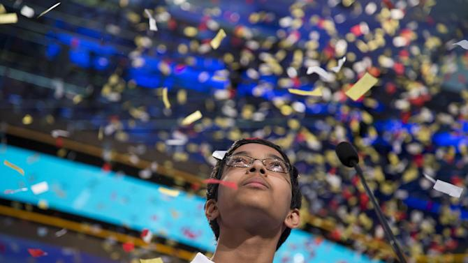 "Arvind Mahankali, 13, of Bayside Hills, N.Y., watches as confetti falls after he won the National Spelling Bee by spelling the word ""knaidel"" correctly on Thursday, May 30, 2013, in Oxon Hill, Md. (AP Photo/Evan Vucci)"