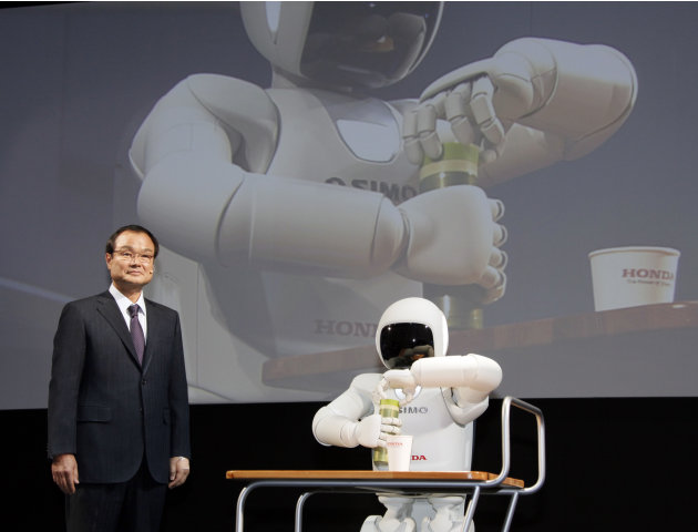 "Honda Motor Co. President Takanobu Ito stands near Honda's human-shaped robot ""Asimo"" at a press conference during the press preview of Tokyo Motor Show in Tokyo, Wednesday, Nov. 30, 2011. The Tokyo M"