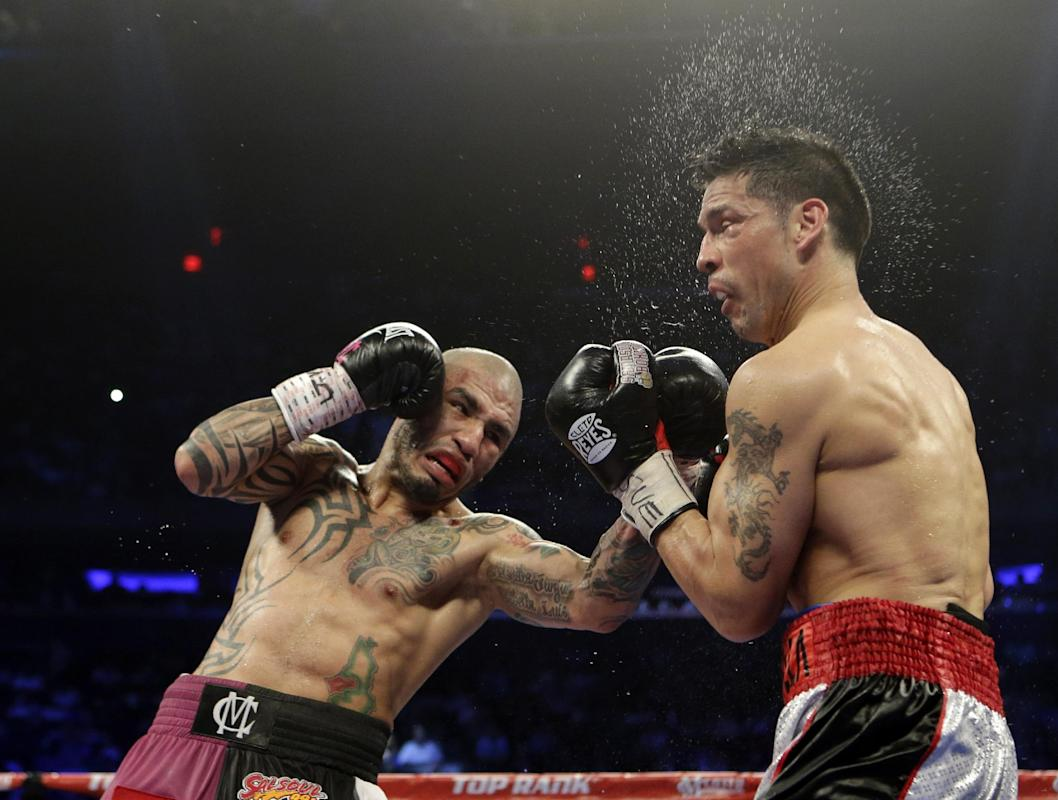 Miguel Cotto, of Puerto Rico, hits Sergio Martinez, of Argentina, during the first ninth round of a WBC World Middleweight Title boxing match Sunday, June 8, 2014, in New York. Martinez stopped the fight after the ninth round