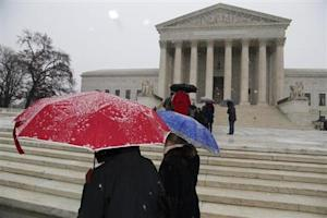 A light snow falls as visitors gather on the steps of the U.S. Supreme Court in Washington