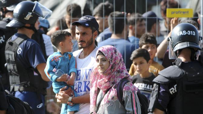 A family of migrants walks as Hungarian riot police stands guard in front of a migrant reception centre in Roszke