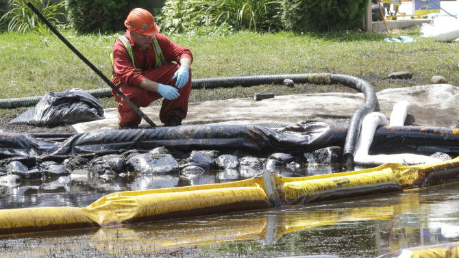 FILE- In this July 29, 2010, file photo, a worker monitors water in Talmadge Creek in Marshall Township, Mich., near the Kalamazoo River as oil from a ruptured pipeline, owned by Enbridge Inc., is attempted to be trapped by booms. On Monday, July 2, 2012, federal regulators proposed a $3.7 million civil penalty against the Canadian owner of the ruptured pipeline which dumped more than 800 million gallons of oil into the river. (AP Photo/Paul Sancya, File)