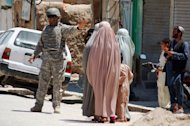 A US soldier stops Afghan women from walking towards the governor&#39;s compound in Kandahar. Two bodyguards and two suicide attackers have been killed in a gun battle inside the the compound, an official said