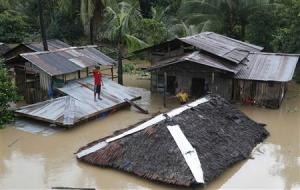 "A resident stands on the roof of his home that is submerged in heavy flooding brought by tropical depression ""Agaton"", in Butuan city"