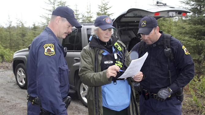 Kenai Police Sgts. Scott McBride, left, and Jay Sjogren review a map with Lisa Jaegar from the Mat-Su Search and Rescue Dogs on Monday, June 9, 2014, in Kenai, Alaska. Two rescue dog teams along with agents with the FBI are searching the wooded area north of Wildwood Correctional Facility for a Kenai family of four, missing since May 27. (AP Photo/Peninsula Clarion, Dan Balmer)