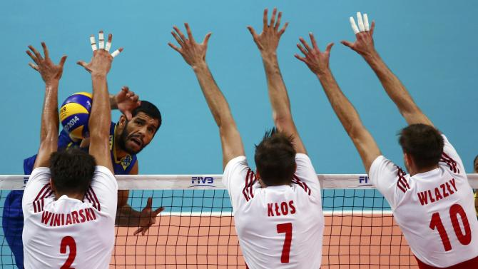 Brazil's De Souza spikes the ball against Poland's Winiarski, Klos and Wlazly during their final match at the FIVB Volleyball Men's World Championship Poland 2014 at Spodek Arena in Katowice