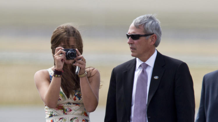 Naomi Biden, left, takes pictures of her grandfather and U.S. Vice President Joe Biden as they arrive at the Chinggis Khaan International Airport in Ulan Bator, Mongolia, Monday, Aug. 22, 2011. (AP Photo/Andy Wong)
