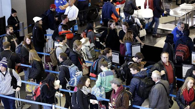 Travelers line up at a security checkpoint area in Terminal 3 at O'Hare International Airport on Sunday, Nov. 29, 2015, in Chicago. Tens of millions of Americans returning home after the long Thanksgiving holiday weekend Sunday have cooperative weather and mostly efficient airport operations to thank for smooth traveling conditions. (AP Photo/Nam Y. Huh)