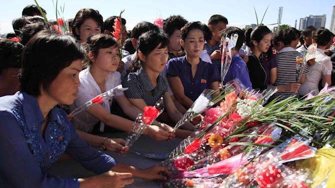 People lay flowers to pay their respects to their late leader Kim Il Sung, at Mansu Hill, where a bronze statue of him and his son, Kim Jong Il stands, Wednesday, July 8, 2015, in Pyongyang, North Korea. This was done to mark the 21st anniversary of Kim Il Sung's death. (AP Photo/Jon Chol Jin)