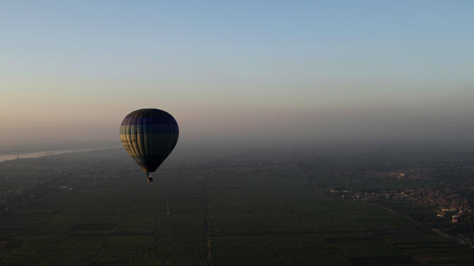 FILE - In this Friday, Nov. 23, 2012 file photo, tourists ride a hot air balloon before sunrise in Luxor, Egypt. On Sunday, April 21,  2013 senior civil aviation official says Egypt has resumed hot air balloon sightseeing flights in the ancient city of Luxor in southern Egypt, weeks after a fiery accident. (AP Photo/Nariman El-Mofty, File)