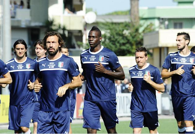 Italy's Mario Balotelli, center,  and Andrea Pirlo lead the group  during a training session with their team at the Giarrusso stadium in the outskirts of Naples, Monday, Oct. 14, 2013, ahead of a 2014