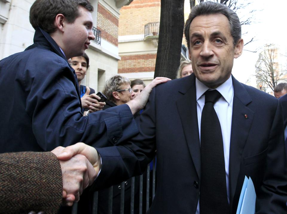 French President Nicolas Sarkozy, right, shakes hands with supporters near his campaign party headquarters, Paris, Thursday, March 22, 2012. Sarkozy said Thursday an investigation was under way to see if the suspect in a series of radical Islam-inspired killings had any accomplices. (AP Photo/Jacques Brinon)