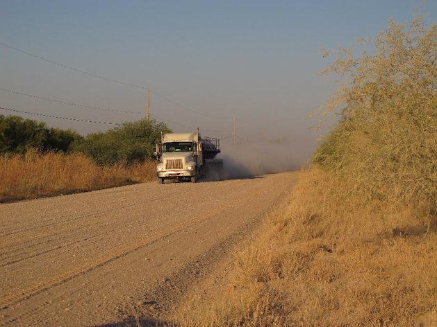 FILE - In a Friday Oct. 26, 2012 file photo, a truck travels along the stretch of gravel road near La Joya, Texas, where a Texas Department of Public Safety helicopter and sharpshooter assisted the previous day in the chase of a suspected illegal immigrant smuggler. Two people in the fleeing vehicle were killed and a third was wounded. A grand jury will consider the case of two Guatemalan immigrants killed in the bed of the tarp-covered truck that authorities thought was ferrying drugs, a prosecutor said Wednesday, Oct. 31, 2012. (AP Photo/Chris Sherman, File)