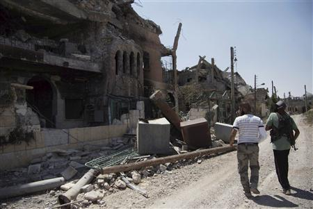 Free Syrian Army fighters walk past damaged buildings and debris in Deir al-Zor