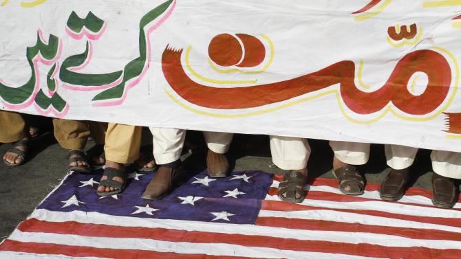 "Pakistani protesters stand on a representation of  the U.S. flag holding a banner that reads ""we condemn,"" to condemn the reported burning of Qurans in Afghanistan by U.S. troops, in Lahore, Pakistan, on Monday, Feb 27, 2012. (AP Photo/K.M.Chaudary)"