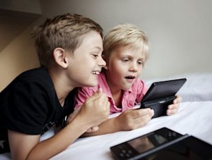 Children playing handheld video games.