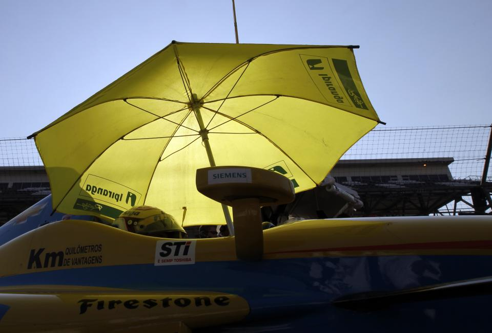 IndyCar driver Ana Beatriz, of Brazil sits in her car under an umbrella during a break in practice on the first day of qualifications for the Indianapolis 500 auto race at the Indianapolis Motor Speedway in Indianapolis, Saturday, May 19, 2012. (AP Photo/Darron Cummings)