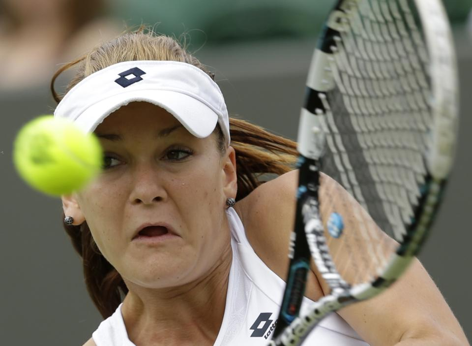 Agnieszka Radwanska of Poland returns a shot to Magalena Rybarikova of Slovakia during a first round women's singles match at the All England Lawn Tennis Championships at Wimbledon, England, Monday, June 25, 2012. (AP Photo/Alastair Grant)