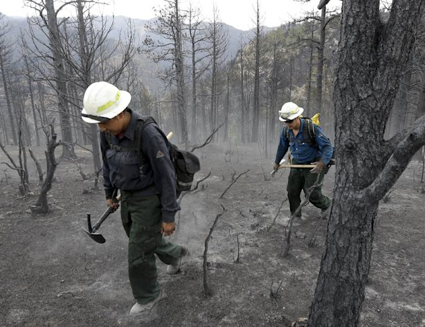 Members of Bighorn 209, a hand crew from the Crow Agency in Montana check for hot spots on the Waldo Canyon Fire west of Colorado Springs, Colo., Friday, June 29, 2012. After declaring a &quot;major disaster&quot; in the state early Friday and promising federal aid, President Barack Obama got a firsthand view of the wildfires and their toll on residential communities. More than 30,000 people have been evacuated in what is now the most destructive wildfire in state history. (AP Photo/Chris Carlson)