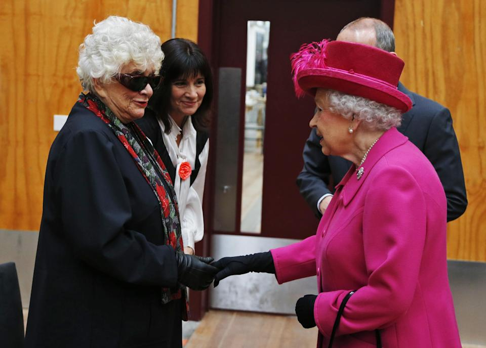 Britain's Queen Elizabeth II, right, meets Lady Olivier, left, widow of Sir Laurence Olivier, during a visit at the National Theatre in London, Tuesday Oct. 22, 2013 to commemorate the institution's 50th anniversary. (AP Photo/Lefteris Pitarakis, pool)