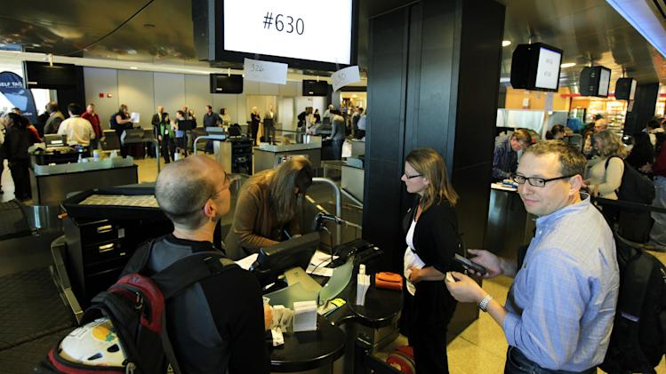 Passengers attempt to manually check in for an Alaska Airlines to Phoenix, Monday, Oct. 8, 2012, at Seattle-Tacoma International Airport in Seattle during a system-wide outage of the computers the airline uses to check in passengers. Some flights were able to be checked in manually, but most flights were delayed or canceled. (AP Photo/Ted S. Warren)