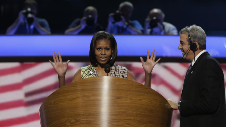 First Lady Michelle Obama appears at the podium for a camera test as head stage manager David Cove, right, instructs on the stage at the Democratic National Convention inside Time Warner Cable Arena in Charlotte, N.C., on Monday, Sept. 3, 2012. (AP Photo/Charles Dharapak)