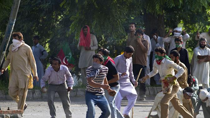 Pakistani protestors throw stones toward the police during clashes that erupted as protestors tried to approach the U.S. embassy, Friday, Sept. 21, 2012 in Islamabad, Pakistan. Protests by tens of thousands of Pakistanis infuriated by an anti-Islam film descended into deadly violence on Friday, with police firing tear gas and live ammunition in an attempt to subdue rioters who hurled rocks and set fire to buildings in some cities.  Four people were killed and dozens injured on a holiday declared by Pakistan's government so people could rally against the video. (AP Photo/Anjum Naveed)