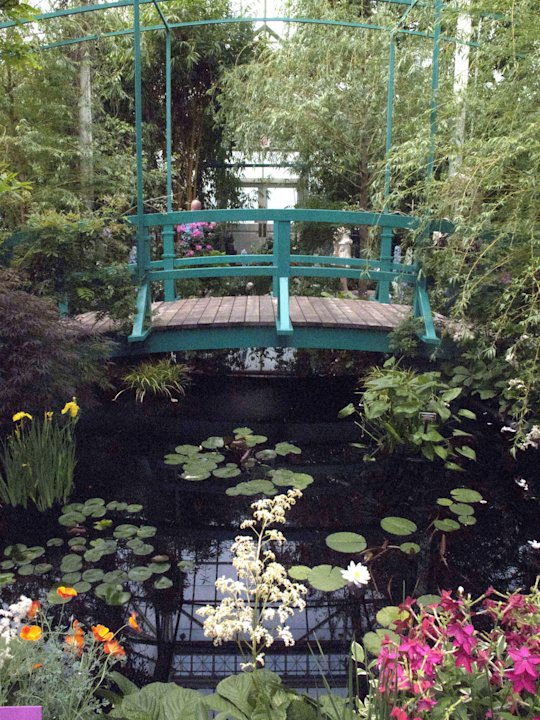 "In this May 26, 2012 photo, a replica of a bridge on the property of artist Claude Monet's home is featured in an exhibition at the New York Botanical Garden in New York.  ""Monet's Garden,"" evokes the"