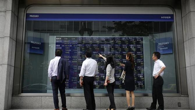 Pedestrians stand in front of a stock quotation board displaying various stock prices outside a brokerage in Tokyo July 29, 2013. REUTERS/Yuya Shino