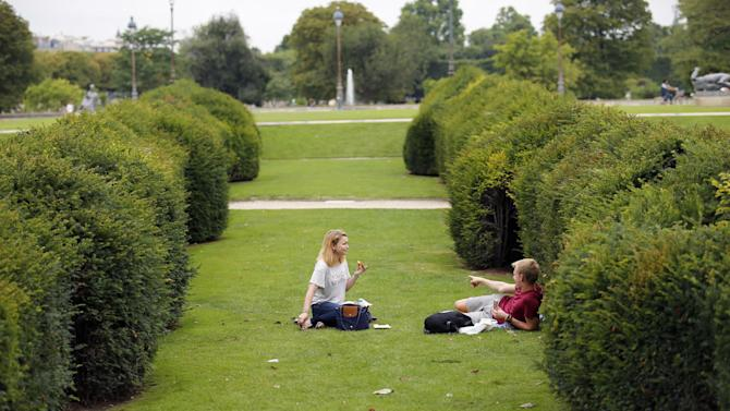 A tourist points out a rat hiding in a hedge to his girlfriend in The Tuileries gardens of the Louvre Muesum in Paris, France, Tuesday, July 29, 2014. Rats have been on the rampage on the grass in broad daylight, defying death threats from sanitation workers. (AP Photo/Francois Mori)