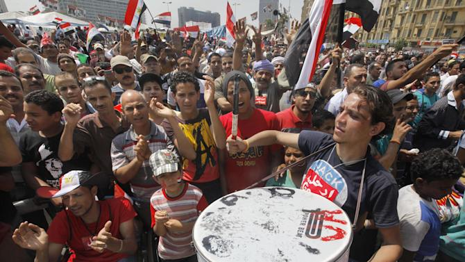 Egyptian protesters shout slogans and wave national flags during a demonstration against Egypt's Islamist President Mohammed Morsi in Tahrir Square in Cairo, Monday, July 1, 2013. Sunday saw millions of Egyptians taking to the streets in Cairo and across much of the nation to demand Morsi's ouster. Egypt's official news agency says five cabinet ministers are meeting to consider resigning their posts and joining the mass protests calling on the Islamist president to step down.(AP Photo/Amr Nabil)