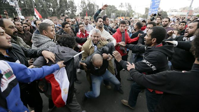 FILE - In this Wednesday, Dec. 5, 2012 file photo, Egyptian President Mohammed Morsi's supporters beat an opponent, center, during clashes outside the presidential palace, in Cairo, Egypt. For most of the 85 years since its inception, the Muslim Brotherhood operated secretively as an outlawed group, working underground and often repressed by governments. But even after its political success since Hosni Mubarak's ouster, the group is still suspected of carrying on secretive operations.  (AP Photo/Hassan Ammar, File)