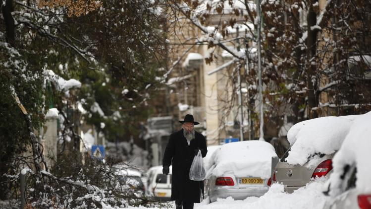 An ultra-Orthodox Jewish man walks on a snow-covered street in Jerusalem