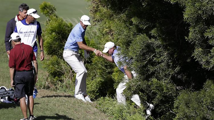 Steve Stricker, right, is helped out of a steep wooded area by Dustin Johnson after the two searched for Johnson's errant ball on the 13th hole during the final round at the Tournament of Champions PGA golf tournament Tuesday, Jan. 8, 2013, in Kapalua, Hawaii. (AP Photo/Elaine Thompson)