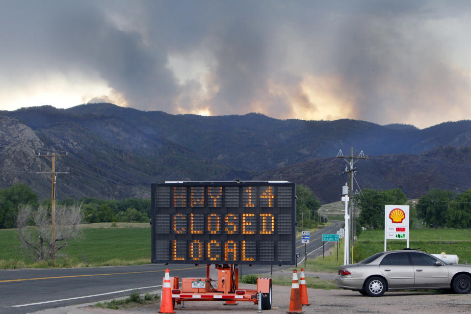 A sign warns motorist of the closure of Highway 14 through Poudre Canyon as columns of smoke rise in the distance from the High Park wildfire west of Fort Collins, Colo., on Friday,  June 15, 2012. The wildfire started Saturday and has burned over 50,000 acres. (AP Photo/Ed Andrieski)