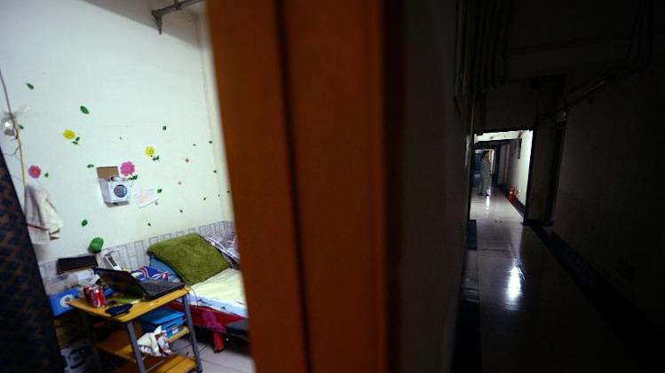 A woman walks through a corridor beneath a building in Beijing, January 14, 2014. About 281,000 people live underground in Beijing according to city authorities