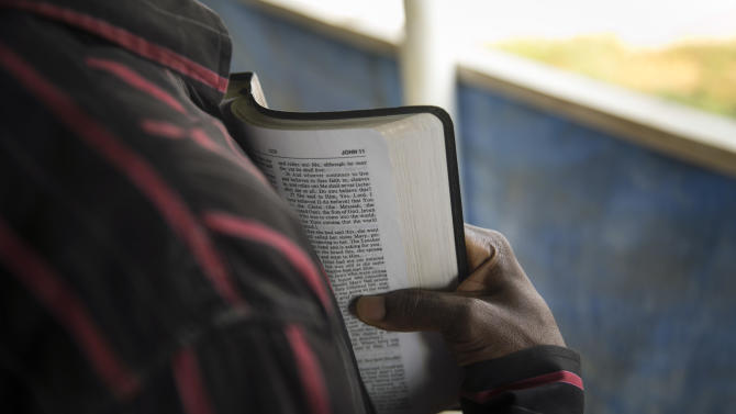 A member of the clergy reads from the Bible to Ebola Patients in the recovery wing of the Hastings Ebola treatment centre in a neighbourhood in Freetown