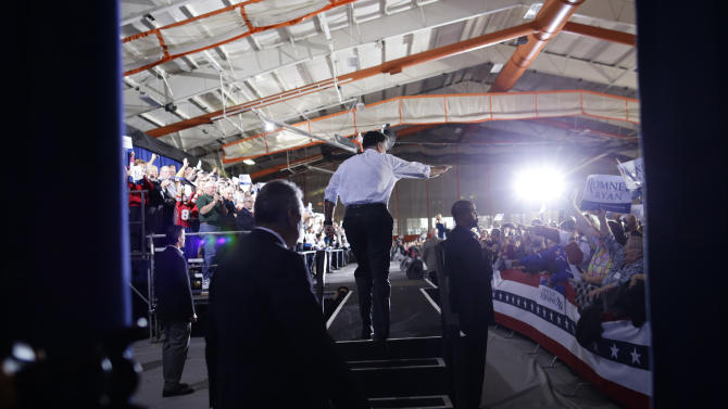 Seen from backstage, Republican presidential candidate and former Massachusetts Gov. Mitt Romney takes the stage at a campaign rally at Koehler Athletic Complex, University of Findlay, Sunday, Oct. 28, 2012, in Findlay, Ohio. (AP Photo/Charles Dharapak)