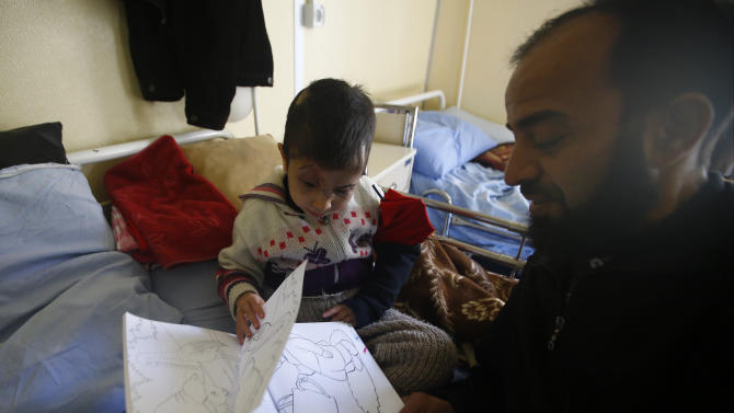 Five-year old Sheima, who lost both eyes when hit by a stray bullet in Syria, sits while her father describes her a colouring book at her hospital bed in a small clinic near the Turkish-Syrian border in the southeastern city of Kilis