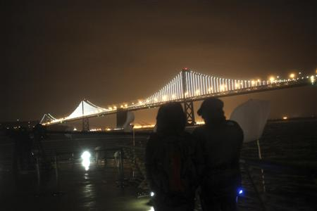 A couple looks out over a lighted art display on the San Francisco-Oakland Bay Bridge in San Francisco