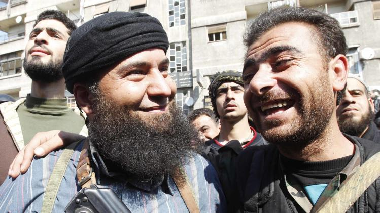 File photo of a soldier loyal to Syria's President Assad joking with a member of Syria's armed opposition forces in Babila town, southeast Damascus, after a local ceasefire agreement was reached